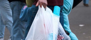 A9YG7C Man at a fair carrying objects in plastic bags